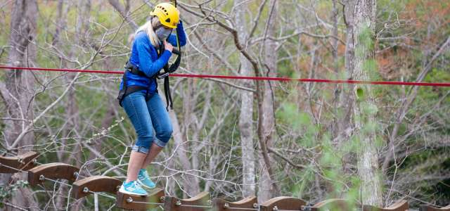 Masked female on Air Hike ropes course
